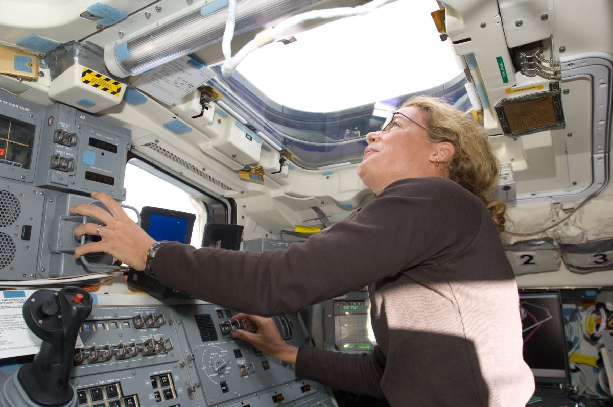 Julie Payette looks through an overhead window while operating the Canadarm controls on the aft flight deck of Space Shuttle Endeavour