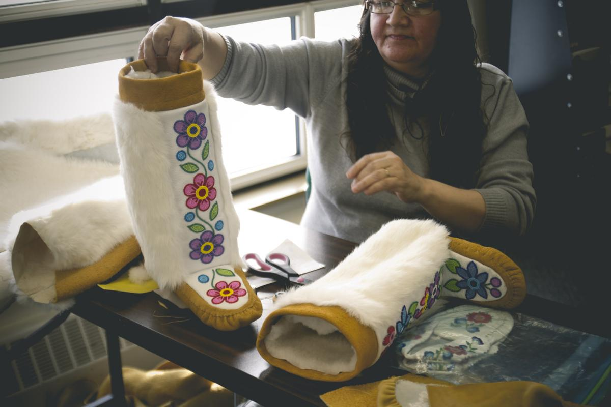 A Cree artist from Manitoba displays a pair of mukluks she created by hand