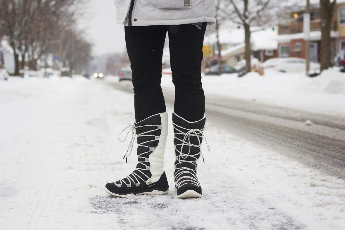 Woman wearing winter boots on a snowy street