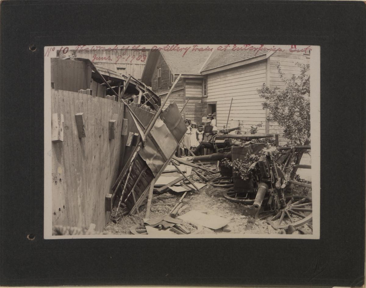 A solemn group of women and children look on at the scene of an artillery train wreck, the debris pushed out in front of them. A lone officer sits with his legs crossed, his gaze directed towards the viewer