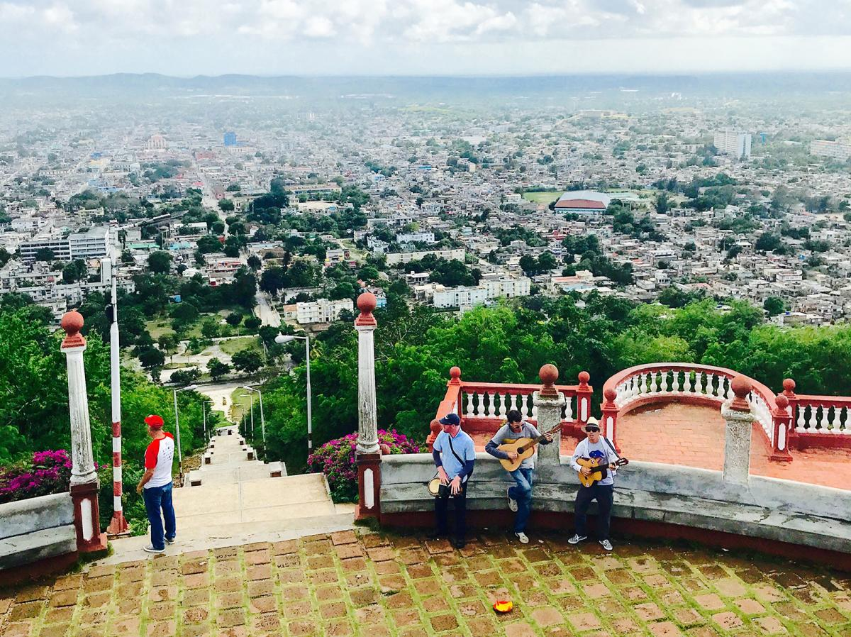 Musicians at the top of Loma de la Cruz in Holguin, Cuba, with a view of the city beyond