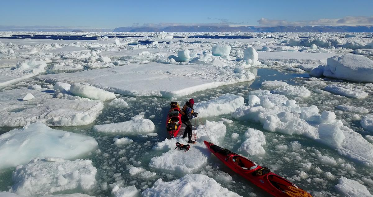 Members of the Enduring Ice Project jump from ice floe to ice floe in Nares Strait during their expedition in the summer of 2017.