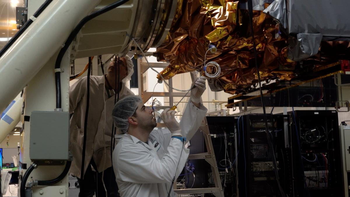 A worker in a flightsuit makes adjustments to a satellite