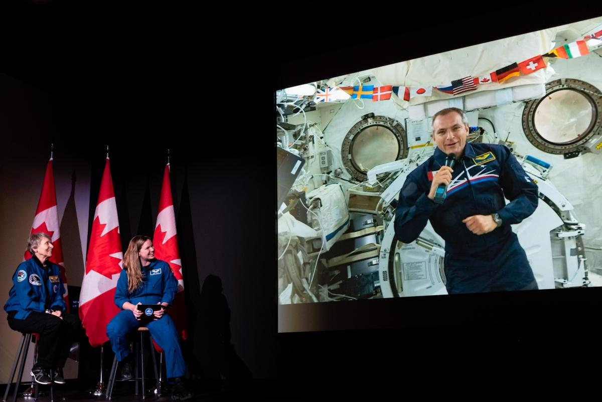 Roberta Bondar, Jenni Sidey-Gibbons, and David Saint-Jacques (appearing via video link from the International Space Station) talk to students at the Canada Museum of Science and Technology