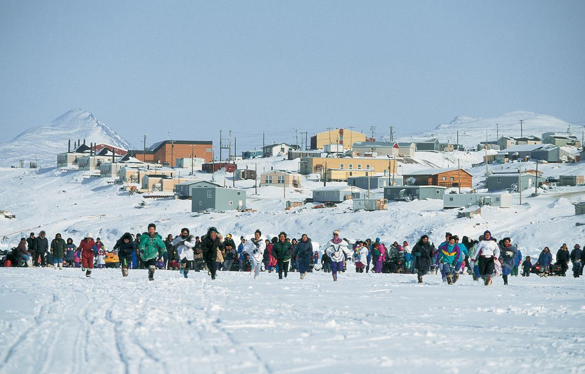 Women in Nunavut running across a snow-covered field towards the camera