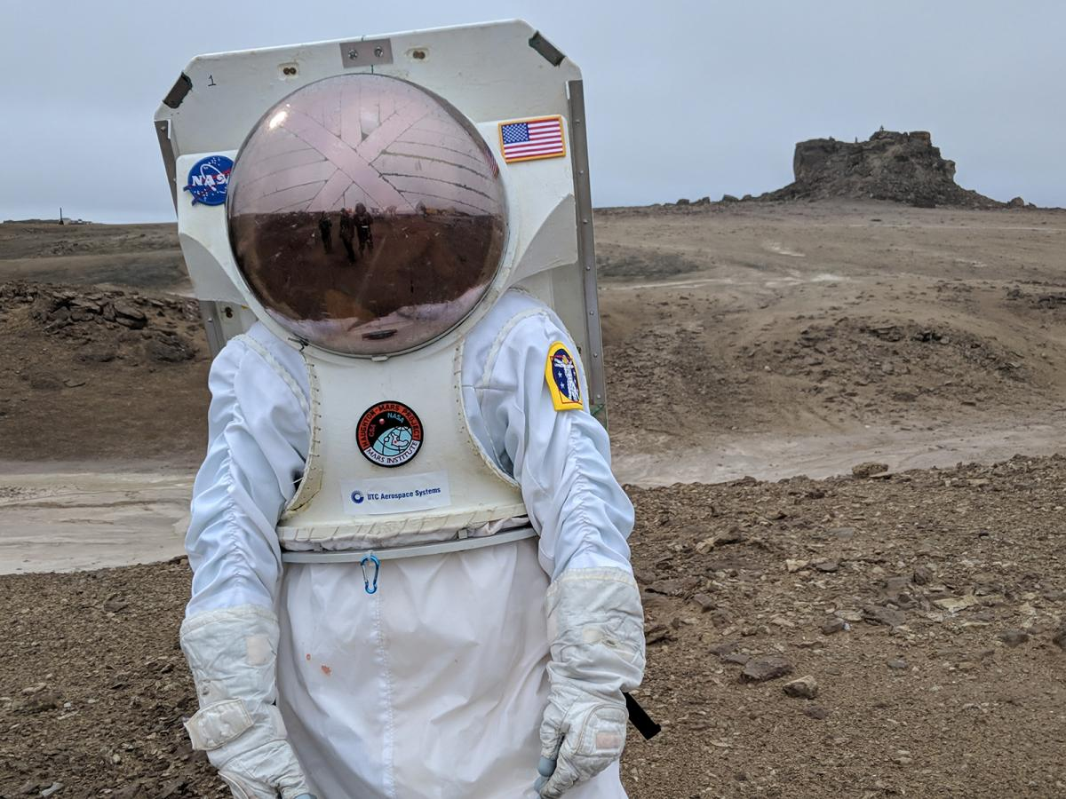 A person in a space suit and helmet stands in front of a rocky, dry landscape on Devon Island