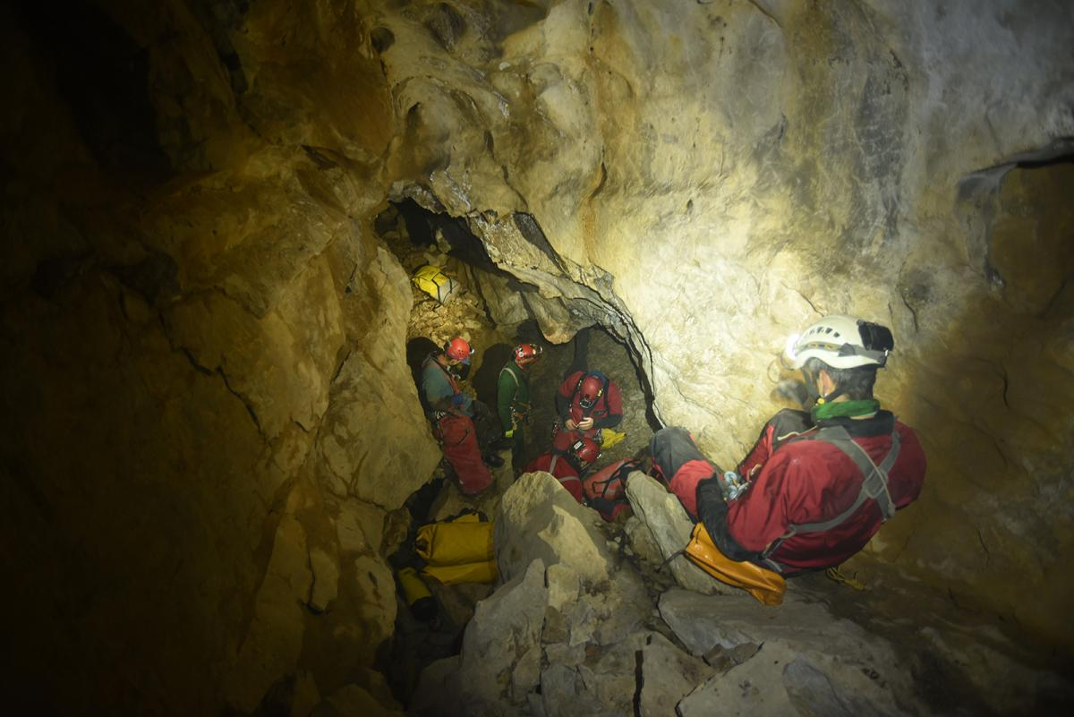 Cavers squeeze through a narrow passage inside Bisaro Anima cave