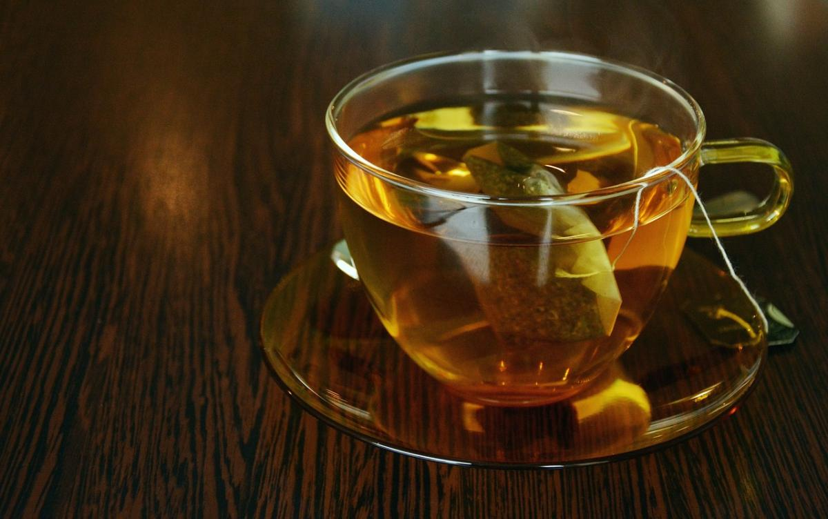 A glass teacup filled with tea, with teabag still in