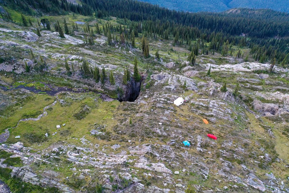 Overhead view of Jawdrop base camp with Claire and Eva watching Robin rig the cave entrance