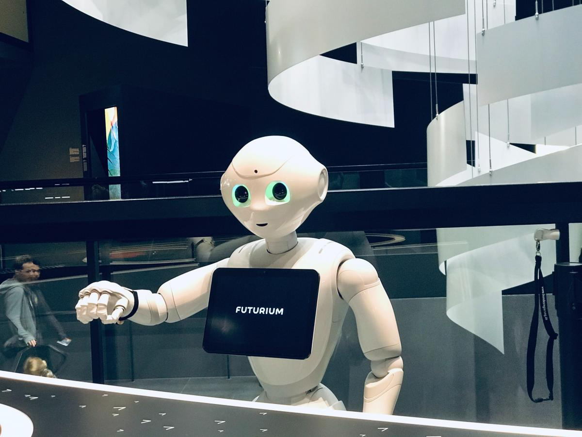 A robot with a tablet stands at a reception desk
