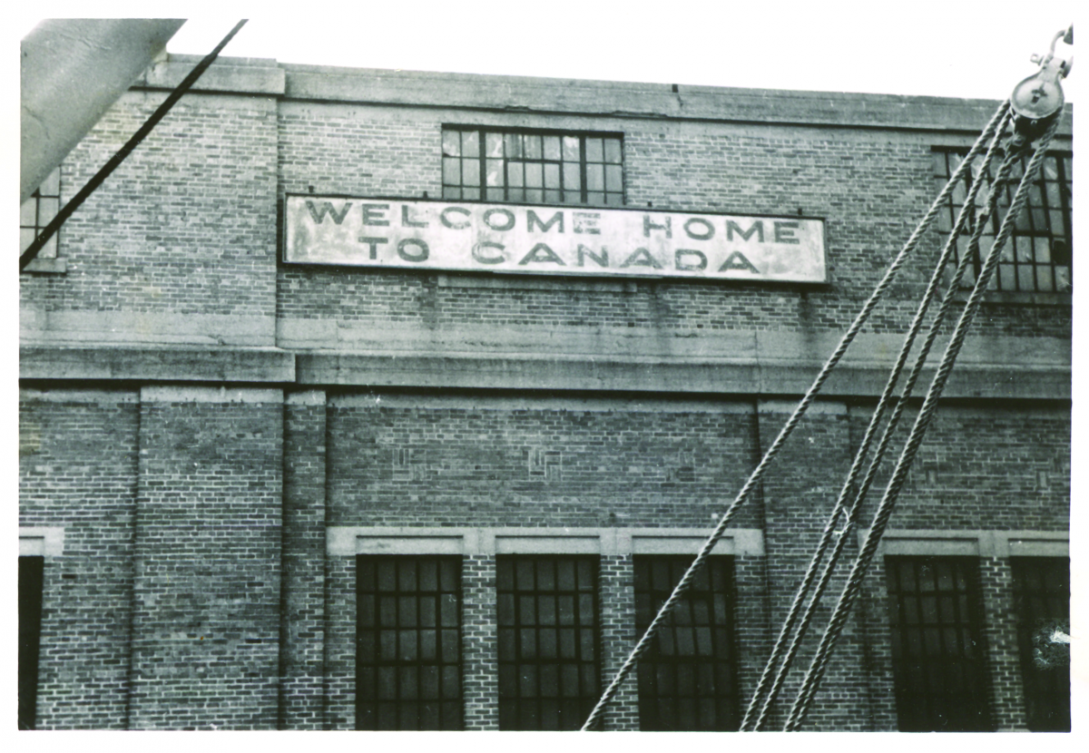 "A Black and white photo of a sign that says ""welcome home to Canada"" on a brick building"