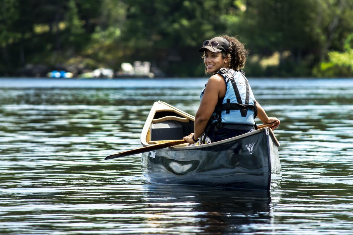 Tori, in her canoe, smiles back towards the camera across glistening blue water