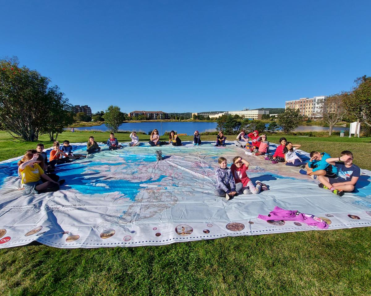 Students sitting on Can Geo Education's Indigenous Peoples Atlas of Canada Giant Floor Map.