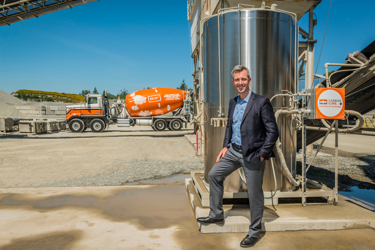 CEO of CarbonCure stands in front of concrete mixer truck and valve box