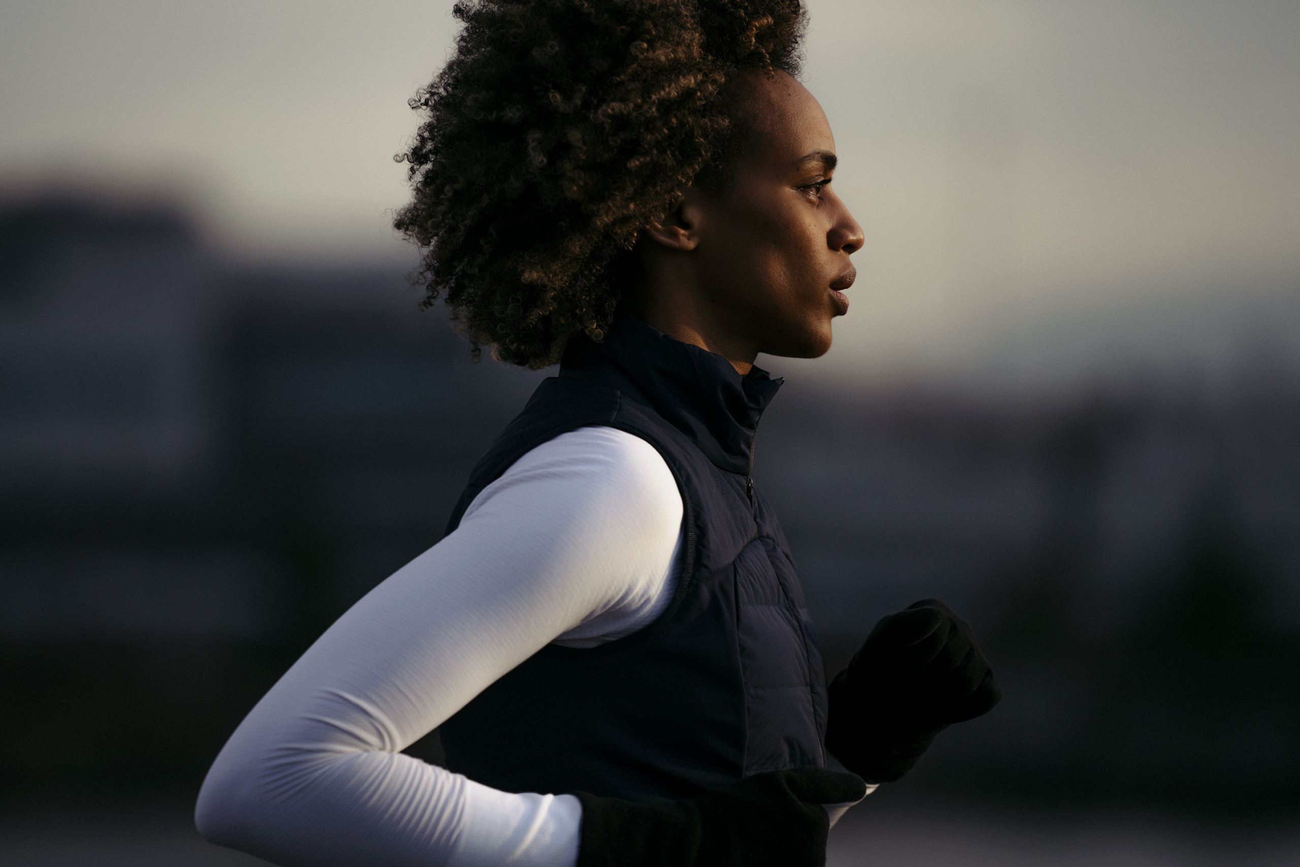 Filsan Abdiaman, a black woman, runs with her face tilted toward the light, the background blurry behind her.