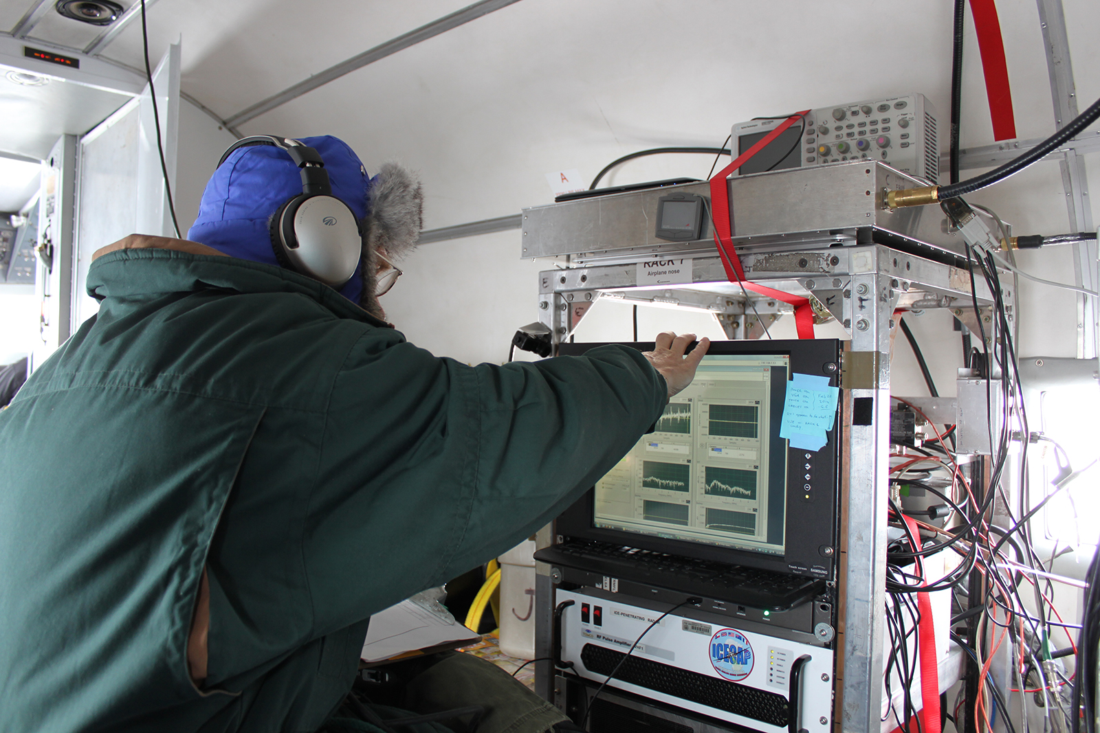 A UTIG research scientist operating the radar instruments inside a DC-3 aircraft during a survey flight over Devon Ice Cap. Photo credit: Anja Rutishauser