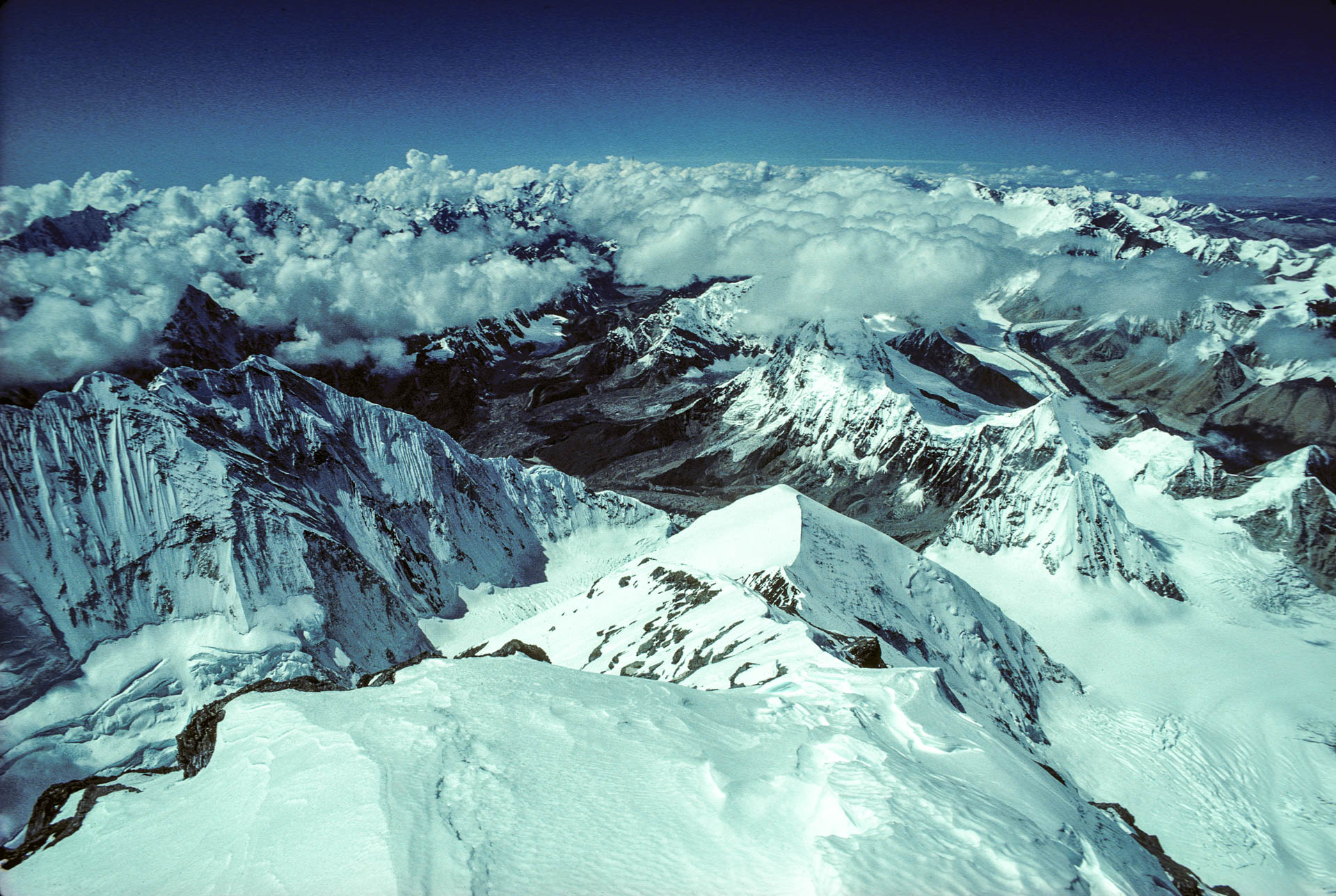 A view of snow covered mountains under a bright blue sky